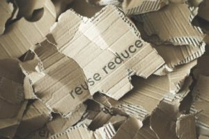 """Scraps of cardboard with the words """"reuse reduce"""" written across to promote cardboard recycling"""